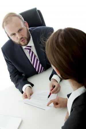 beard business man brunette woman at desk signs contract Standard-Bild