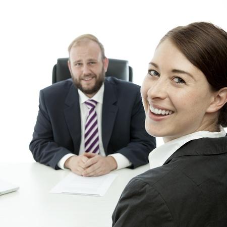 beard business man brunette woman at desk smiling