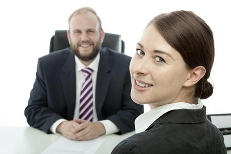 beard business man brunette woman at desk smile