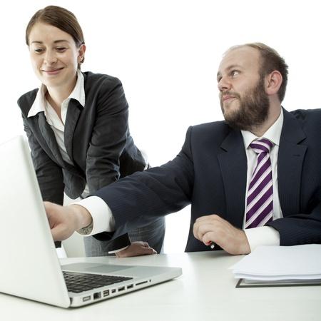 beard business man brunette woman at desk point at laptop photo