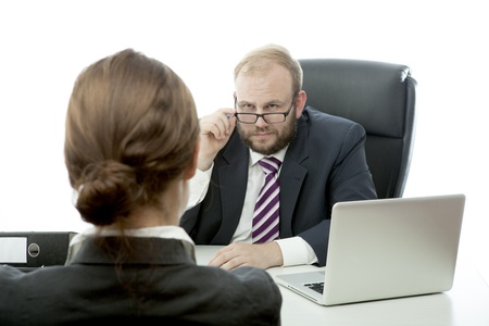 beard business man brunette woman at desk looking serious
