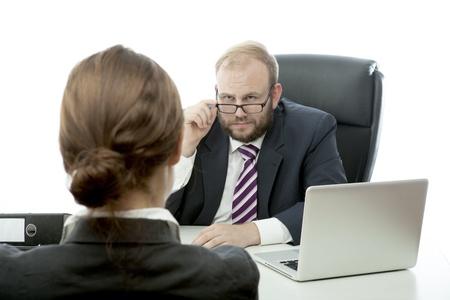 interview: beard business man brunette woman at desk looking serious