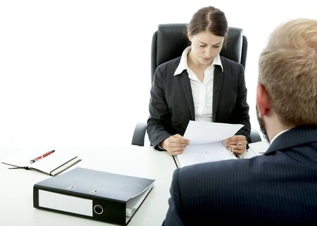 beard business man brunette woman at desk read application Stock Photo