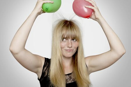 electric charge: young beautiful blond haired girl with electric loaded balloons in front of grey background Stock Photo
