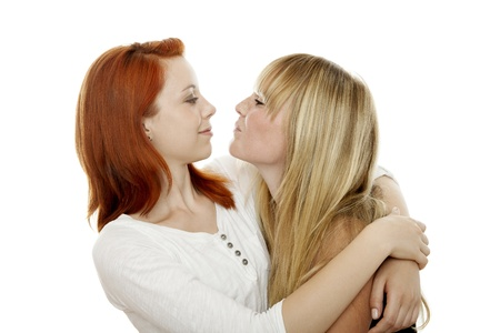 young beautiful red and blond haired girls kissing in front of white background