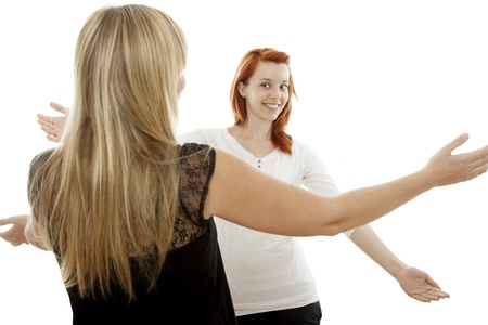 again: young beautiful red and blond haired girls want to give a hug in front of white background