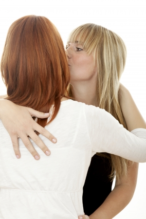 young beautiful red and blond haired girls kissing in front of white background photo