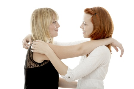 young beautiful red and blond haired girls hugging in front of white background photo