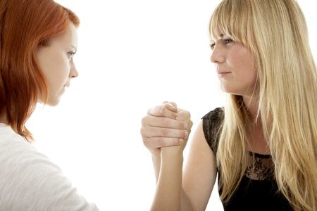 young beautiful red and blond haired girls arm wrestling in front of white background photo