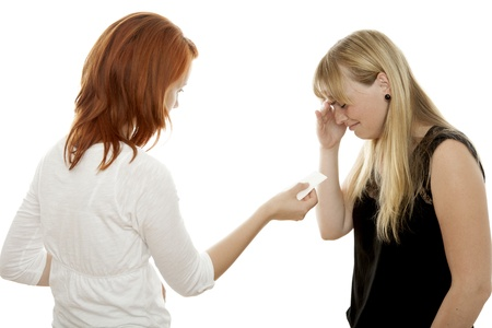 human relations: young beautiful red and blond haired girls cry in front of white background