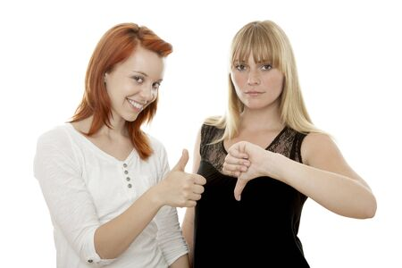 young beautiful red and blond haired girls thumb up and down in front of white background photo