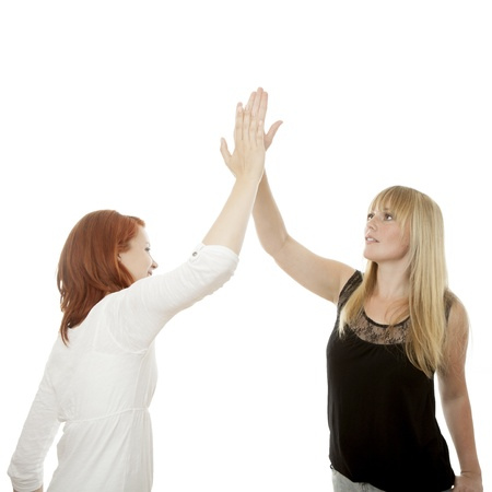 young beautiful red and blond haired girls high five in front of white background