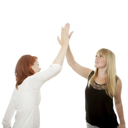 jonge mooie rode en blonde haired girls high five in de voorkant van een witte achtergrond