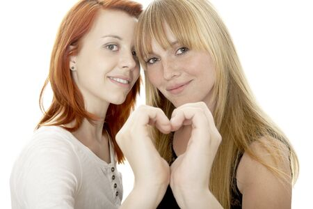 blond haired: young beautiful red and blond haired girls forming heart of hands in front of white background