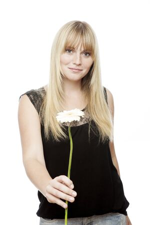 young beautiful blond haired girl gives you a flower in front of white background photo