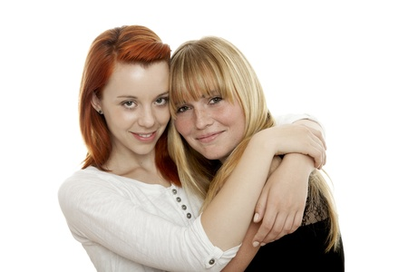 young beautiful red and blond haired girls are best frinde in front of white background photo