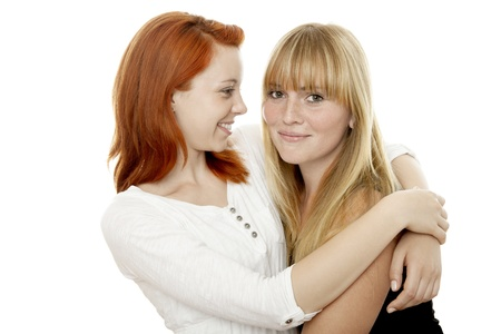 young beautiful red and blond haired girls like each other in front of white background Stock Photo - 15353163