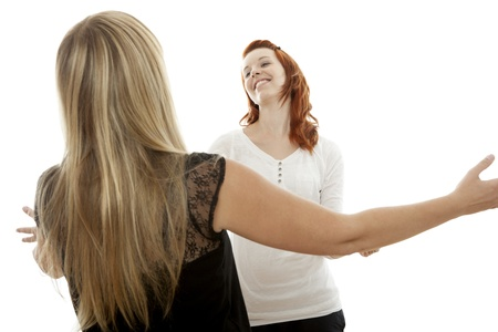 again: young beautiful red and blond haired girls are happy to meet again in front of white background