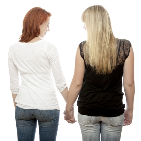 shy girl: young beautiful red and blond haired girls holding hands on back in front of white background