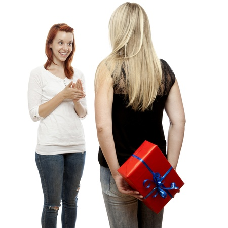 young beautiful red and blond haired girls hide present box behind back in front of white background