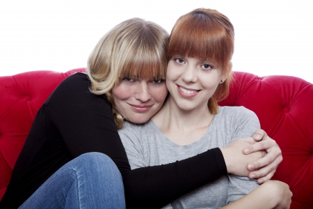 young beautiful blond and red haired girls hug while sitting on red sofa in front of white background