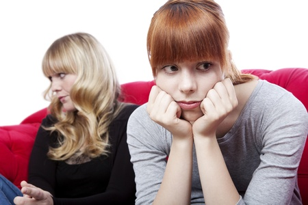 young beautiful blond and red haired girls sitting on red sofa and are sad and depressed in front of white background Standard-Bild