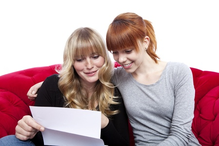 young beautiful blond and red haired girls on red sofa reading letter in front of white background