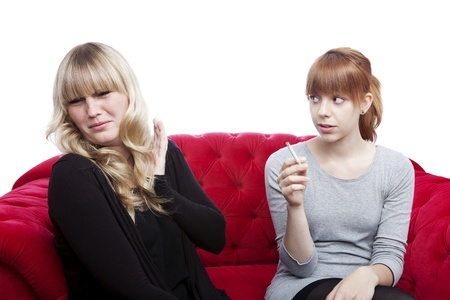 anti smoking: young beautiful blond and red haired girls is disgusting becuase of smoker on red sofa in front of white background
