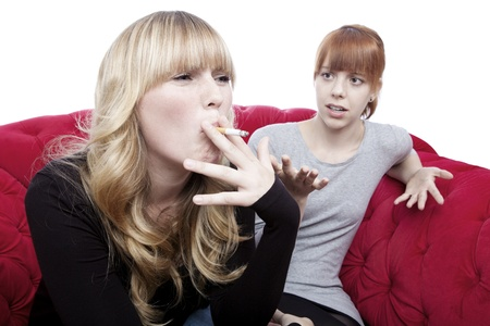 young beautiful blond and red haired girls is shocked about friend smoking on red sofa in front of white background photo