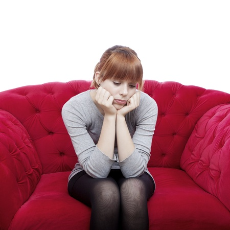 young beautiful red haired girl sit alone on red sofa in front of white background Stock Photo - 15716461