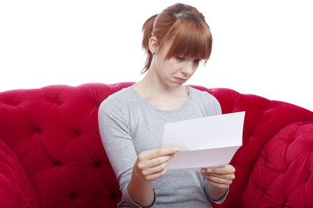 young beautiful red haired girl get bad news on red sofa in front of white background Stock Photo - 15716445