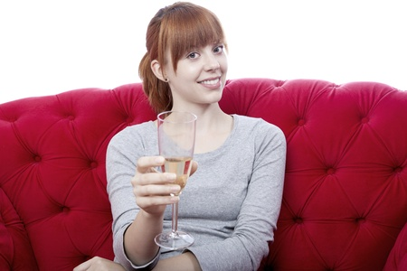 young beautiful red haired girl on red sofa cheers with you in front of white background photo