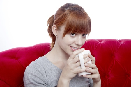 red haired: young beautiful red haired girl on red sofa with cup of tea in front of white background Stock Photo