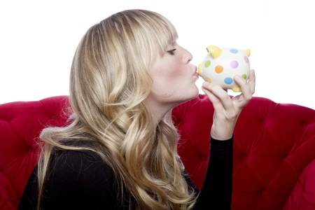 young blond haired girl on red sofa kisses piggybank in front of white background photo