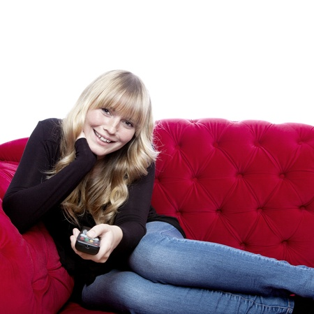 changing channel: young blond haired girl on red sofa happy with remote control in front of white background Stock Photo