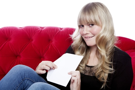 young blond haired girl has a romance and got a letter on red sofa in front of white background Stock Photo - 15716433
