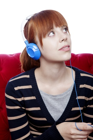 red couch: young beautiful red haired girl on red sofa listen to great music in front of white background Stock Photo