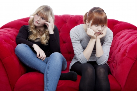 young beautiful blond and red haired girls are bored and depressed on red sofa in front of white background