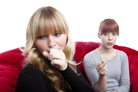 disgusting: young beautiful blond and red haired girls on red sofa in front of white background