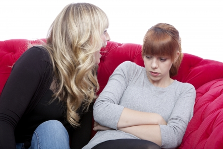 young beautiful blond and red haired girls on red sofa have a fight in front of white background