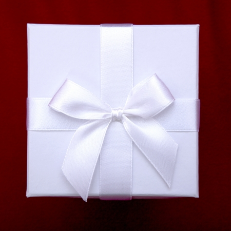 beautiful white gift box with ribbon on top of red sofa background photo