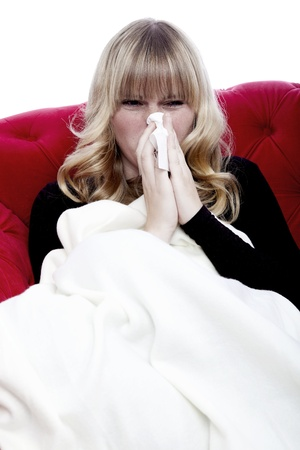 young beautiful blond haired girl with hanky and illness on red sofa in front of white background Stock Photo