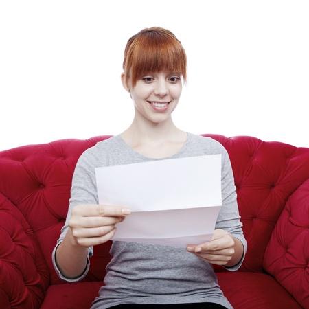 jonge mooie roodharige meisje op rode bank lezen van een brief voor witte achtergrond Stockfoto