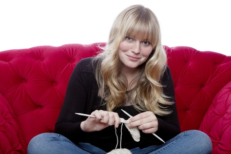 young blond haired girl on red sofa knitting in front of white background