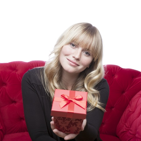 young blond haired girl has a present box for you on red sofa in front of white background photo
