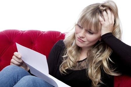 jonge blonde haired meisje op rode bank heb slecht nieuws voor witte achtergrond