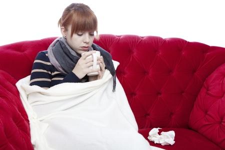 jonge mooie rode haired meisje op rode sofa heeft een koude in de voorkant van een witte achtergrond Stockfoto