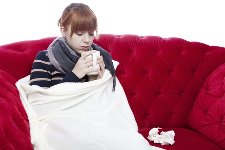 young beautiful red haired girl on red sofa has a cold in front of white background