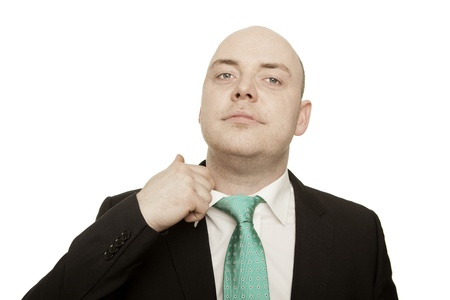 Low angle view of a stressed, hot or nervous businessman loosening his tie with his finger isolated on white photo
