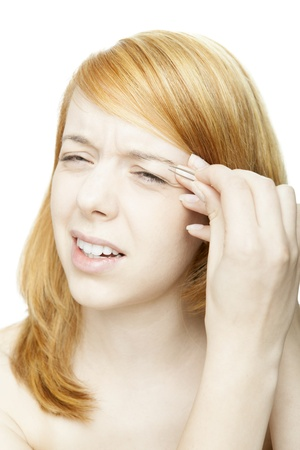 squinting: Attractive young redhead woman plucking her eyebrows with a pair of tweezers squinting in concentration , head portrait isolated on white